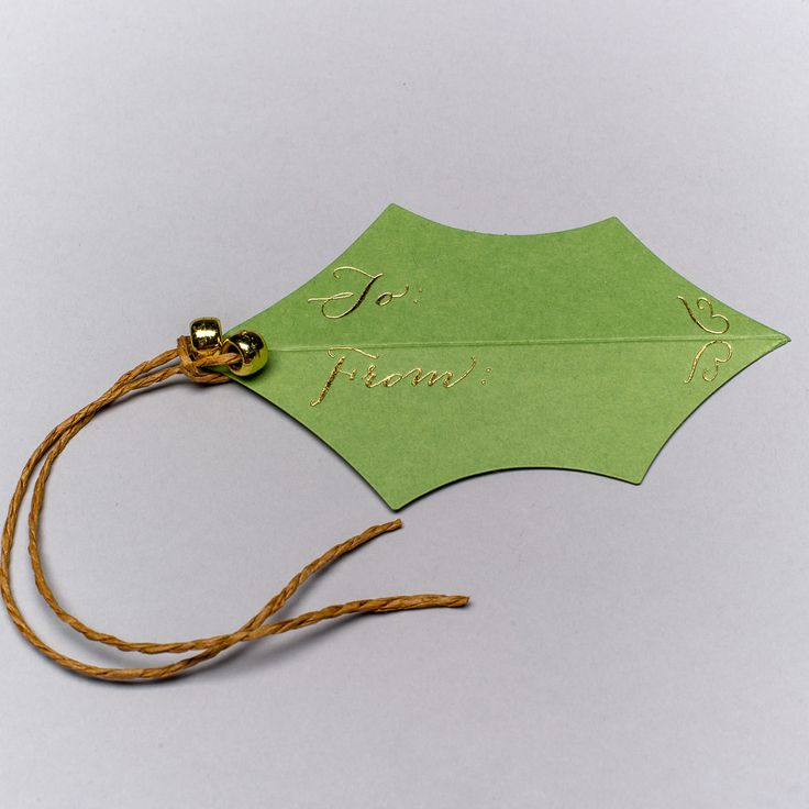 Paper: Green Sold As: Box of 5 holly gift tags with ties and gold beads Detail: Gold foil lettering made in the usa