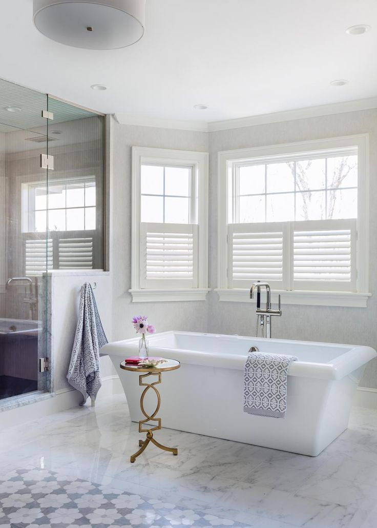 Layered with plush purple and gold furniture, this master suite from Tiffany Leblanc feels warm and regal.In the connecting bathroom, the design gives way to a wash of white, where marble floors and a free-standing tub create a dreamy setting.