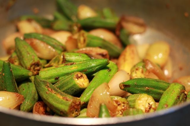 Spicy fried okra is delicious Indian dish that might be served with rise or naan bread. Okra is a vegetable whose texture var
