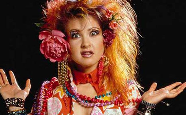 "Cyndi Lauper is a singer-songwriter who reached stardom with hit singles ""Girls Just Wanna Have Fun"" and ""Time After Time"". Her dazzling colorful fashion, which ruled the MTV airwaves, is quintessential 80s style."