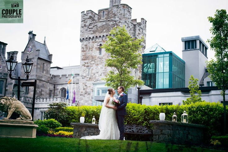 The happy newlyweds in front of the amazing castle. Weddings at Clontarf Castle Hotel by Couple Photography.