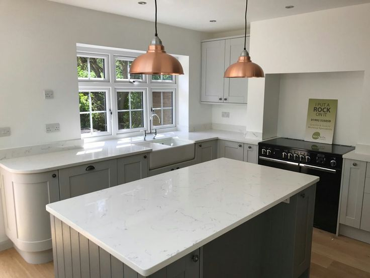 This beautifully traditional kitchen has been incorporated with the Carrera from the Quartz range. The country style of this kitchen matches amazingly with the solid white of the quartz. The customer has decided to jazz up their theme with copper style lighting hanging from the ceiling above the island. This is a perfect contrast and an attractive design for all who enters.
