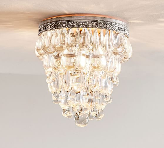 Hundreds of glass droplets form a shimmering cascade on this chandelier its suspended from an antique silver filigreed crown