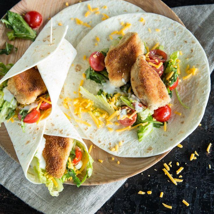 Ein echter Leckerbissen: Knuspriges Hähnchen, mit Salat, Tomaten und Cheddar eingerollt in Tortillas - schnell gemacht und zum Reinbeißen gut.