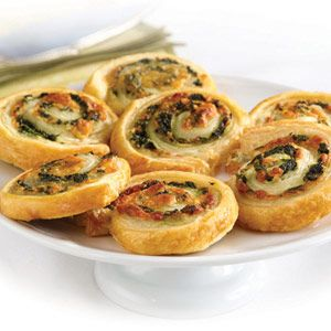 These tempting appetizers look like they're difficult to make...but they're not. They feature a spinach, onion and cheese filling simply rolled up in flaky puff pastry and sliced into pinwheels.
