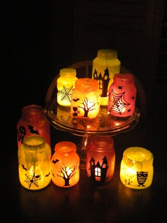 Halloween luminaries - so fun! First we mixed white glue and colored craft paint and painted the inside of glass jars.  Then we decorated the outside of the jars with black vinyl Halloween motifs cut on the Cricut....they are starting to look spooky! Then we put candles in them and turned out the lights! ~!~if you don't own a vinyl machine: paint the designs on w/ black acrylic craft paint