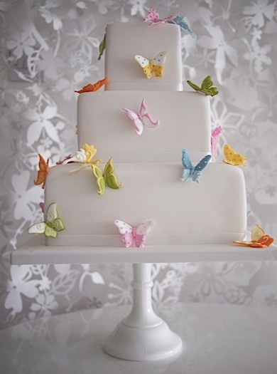 Beautiful cake with scattering of different colored butterflies.