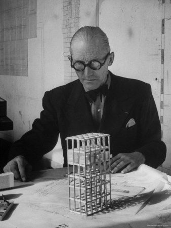 Architect Le Corbusier Studying Architectural Plans and Small Model of Building in His Office