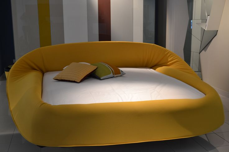 """LAGO  Prodotto: COLLETTO  Come sarebbe dormire avvolti da una barriera visiva e sonora, che corre tutto intorno al materasso? Colletto è un letto comodo e accogliente come un nido. Il soffice anello di """"soft foam"""" intorno al materasso può essere arrotolato e srotolato come il collo di un dolcevita. Il letto acquista un volto sempre diverso, a seconda che il """"collare"""" sia aperto, semichiuso o completamente chiuso per uno spazio ancora più intimo. Sfoderabile."""