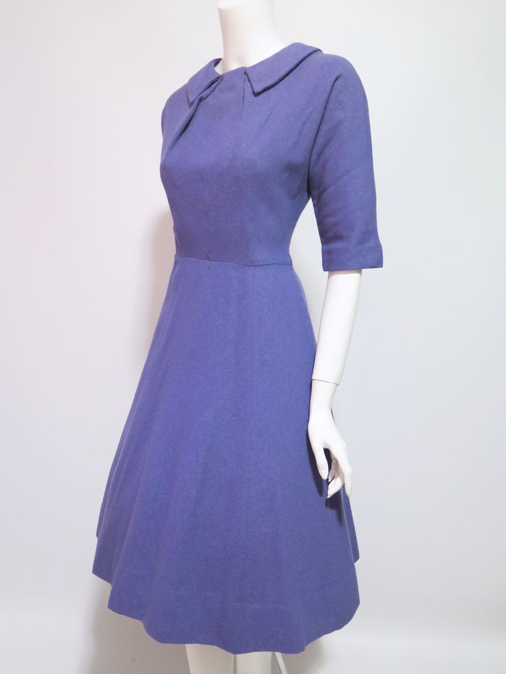 Purple wool day dress from the 1950s with pleated detail at the bust, three-quarter kimono-cut sleeves, nipped waist, and moderately full skirt. Wear it with or