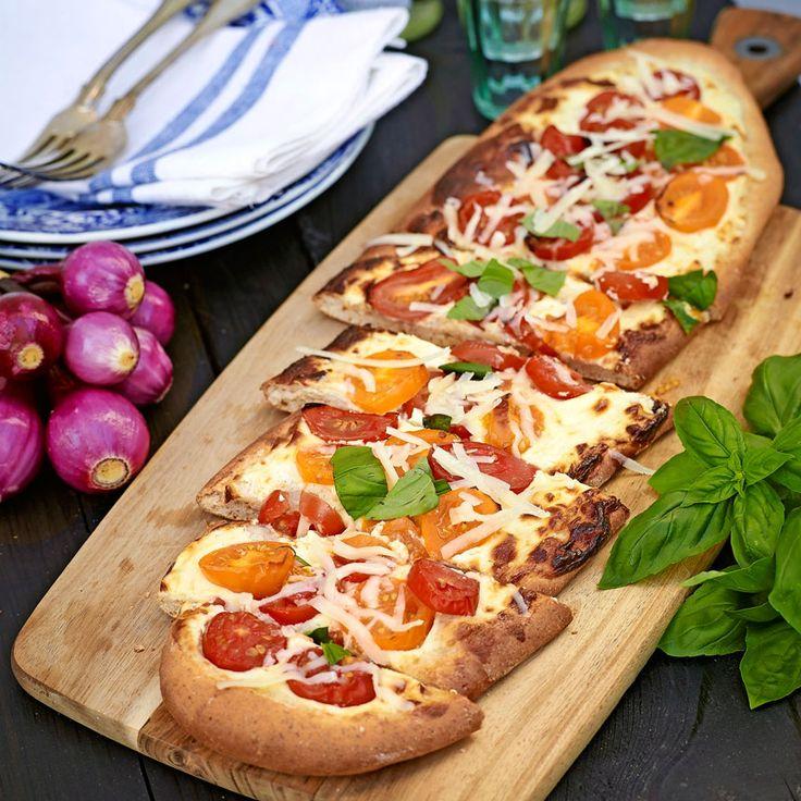 Underbart god pizza med tomater, ost och färsk basilika.