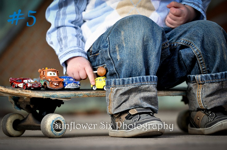 Cute pose for a little boy with his skateboard and Cars