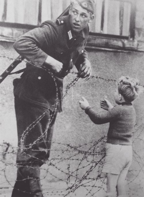 An East German soldier helping a boy cross the newly formed Berlin Wall,  From what is known, the photograph was taken the day the emerging Wall was put up in August 1961 and the boy was found on the opposite side of the wall from his family. Despite given orders by the East German government to let no one pass, the soldier helped the boy through the barbwire.