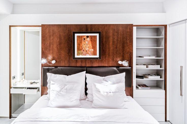 V ložnici má dřevo stejné barevné ladění dřeva. Úložné prostory jsou chytře ukryty ve vestavěném systému, který je snadno přístupný posunutím čelních panelů