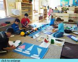 Montessori: Elementary-using lap desks on the floor: