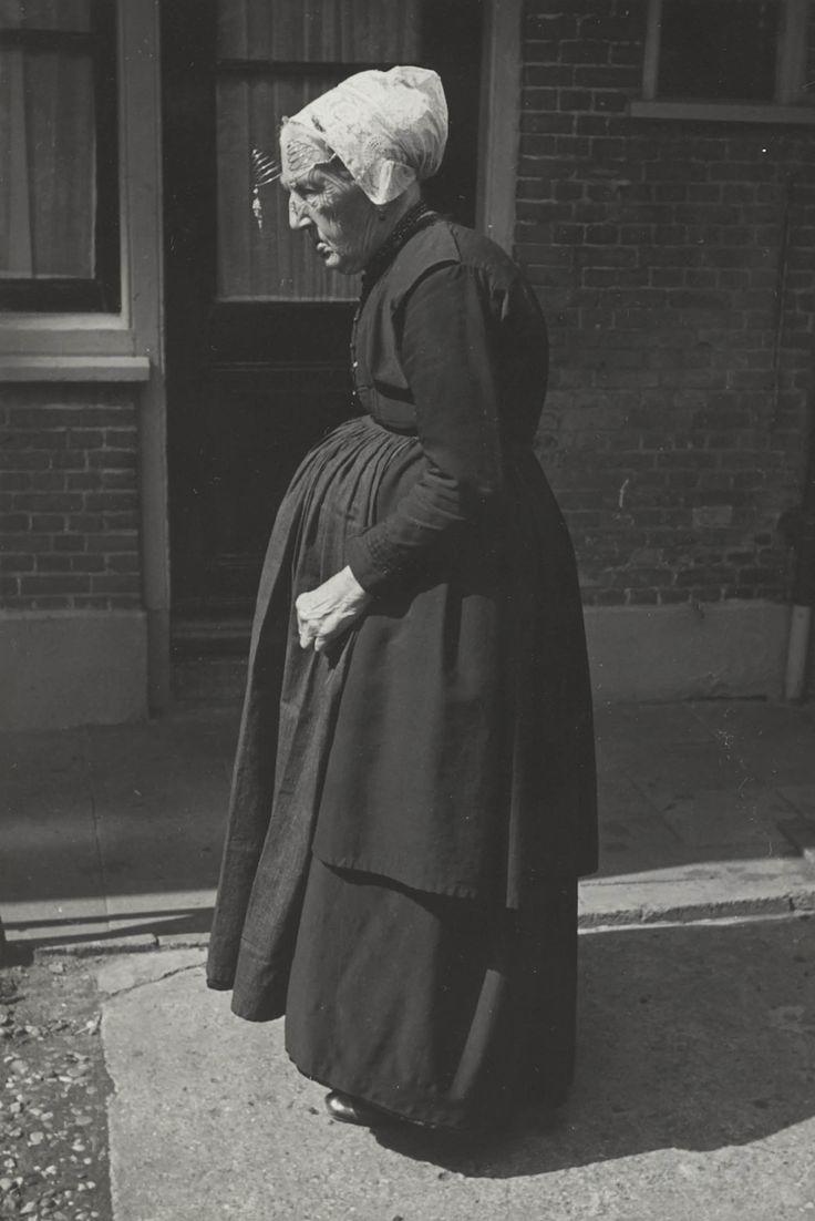 Maria van der Zwan-Moerman in Vlaardingse streekdracht (geboren 1862). Ze is gekleed in zondagse dracht. Ze draagt een schootjak met lange schoot, rok en een schort zonder 'gatbanden'. Op haar hoofd een zwarte ondermuts, een zilveren oorijzer met gouden krullen aan de uiteinden en daarover de 'oorijzermuts'. Aan de krullen hangen oorijzerhangers. Achter de krullen is een paar mutsenspelden in de muts gestoken. 1950 #ZuidHolland #Vlaardingen