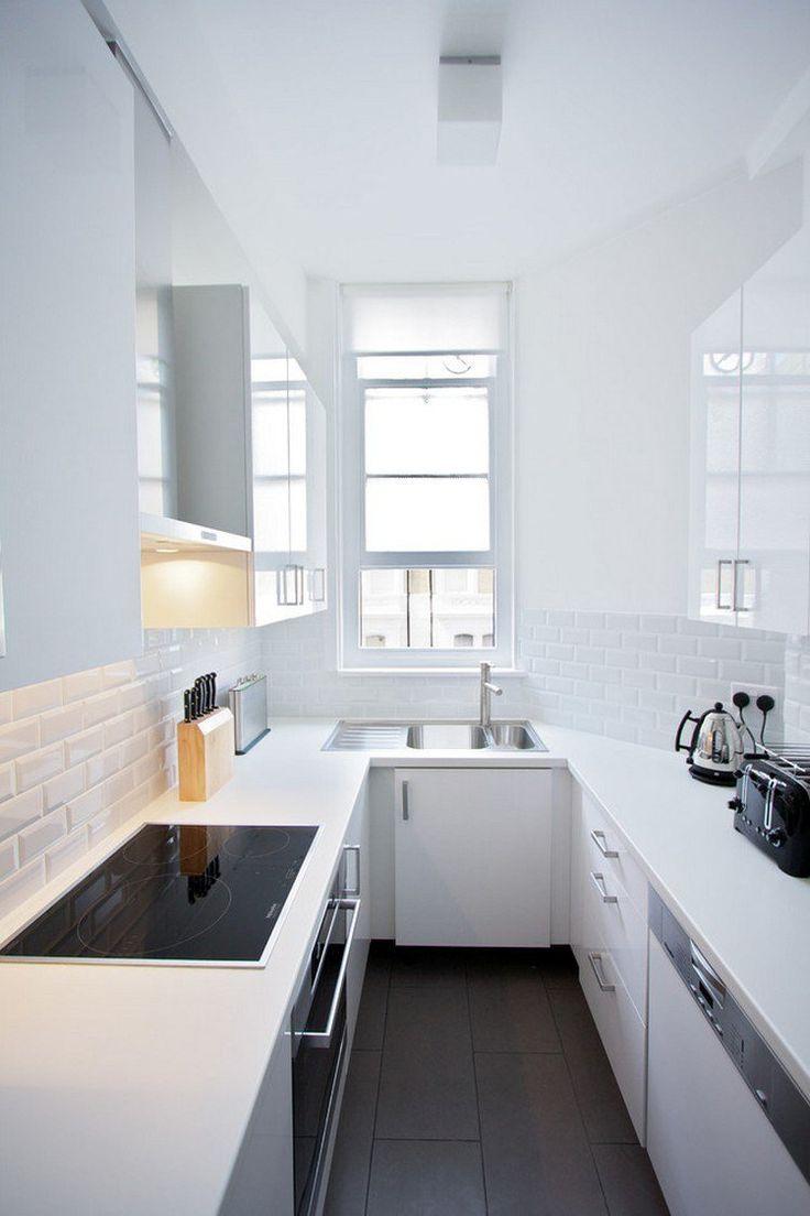 cuisine en U en longueur avec fenêtre, armoires blanches et carrelage métro