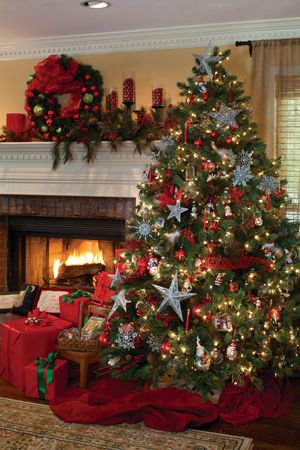 Pick a repeatable motif—like the stars on this tree—to unify your décor. A cozy, crackling fire pairs perfectly with traditional red and green accents. The tree's meaningful collectibles, silver stars, and snowflakes gave it a theme. The mantel decorations and gifts under the tree also reflect traditional Christmas style.