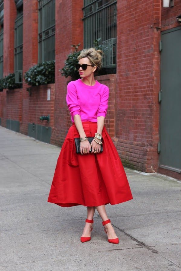 Shop this look on Lookastic:  https://lookastic.com/women/looks/crew-neck-sweater-midi-skirt-pumps/7916  — Red Suede Pumps  — Red Pleated Midi Skirt  — Black Leather Clutch  — Gold Watch  — Hot Pink Crew-neck Sweater  — Dark Brown Sunglasses