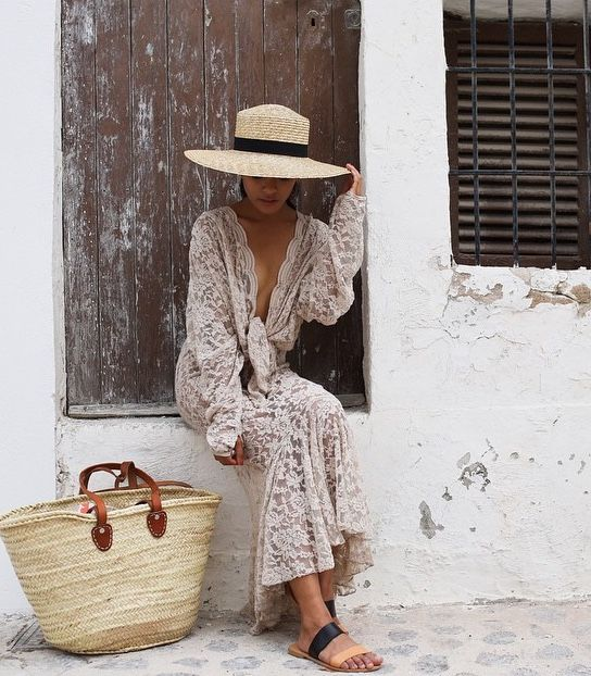 Summer outfit with an off-white lace dress, a straw bag and a hat.