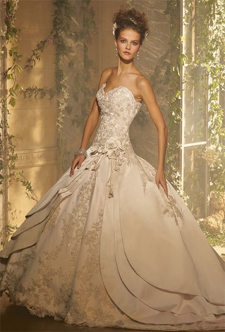 Amalia Carrara. Silk ballgown embroidered in gold and silver, with flower applique on side.