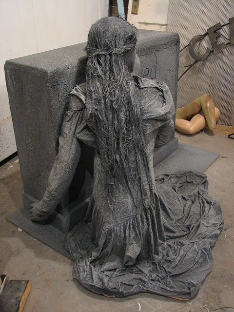 Made from chicken wire, wood, foam, mannequin hands, foam head, dress, then coated with a mixture of joint compound and exterior latex paint (called monster mud).