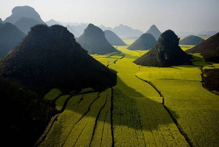 The Chocolate Hills, Philippines -- a perfect uniform shape and the height is about 30-50 m.  Probably formed by self-destruction of an active volcano.  According to legend, they were formed from the tears of a giant who lost his love.