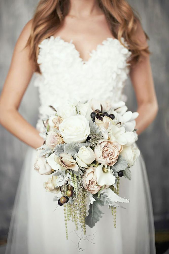 Cozy sweaters and half-length coats look chic with any wedding gown and create opportunity for stunning winter wedding bouquets.