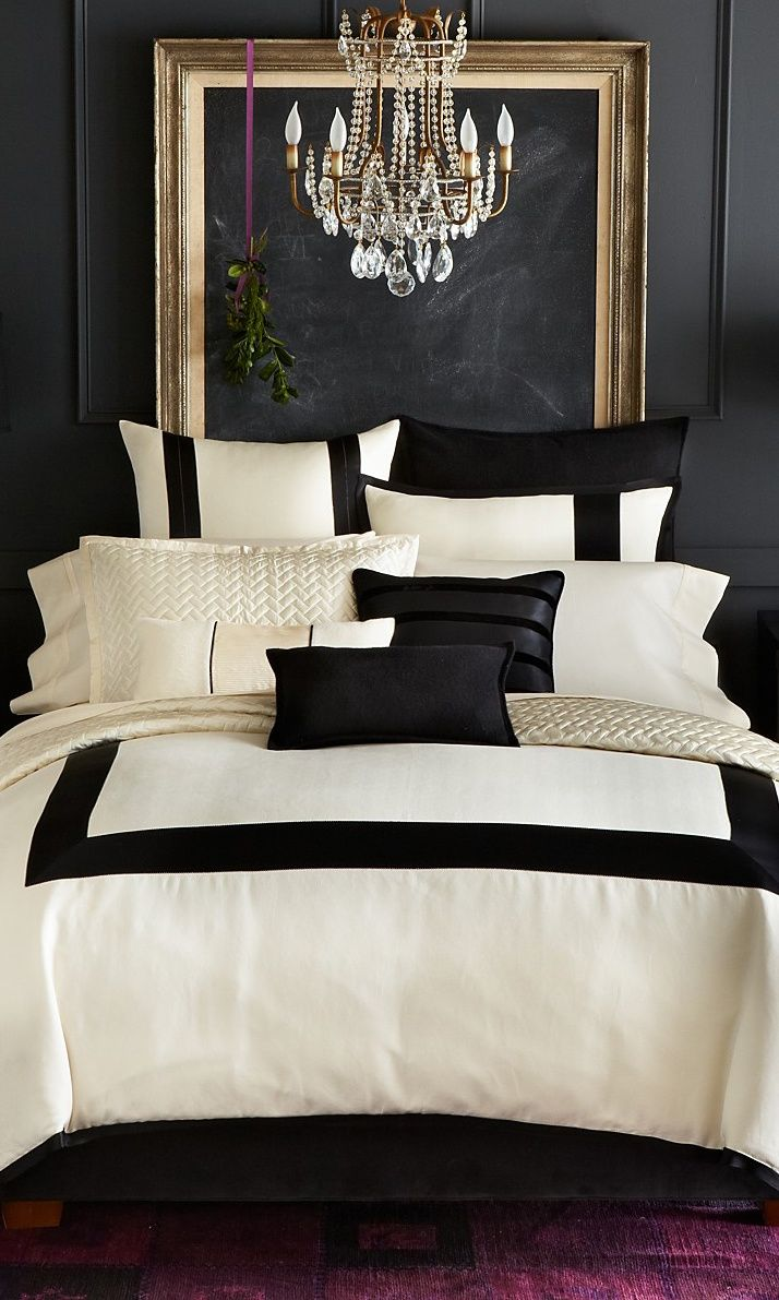 Black and white bedrooms with color accents - Luxurious Cream Black Bedding Against A Pure Black Wall With Gold Framed Blackboard Purple