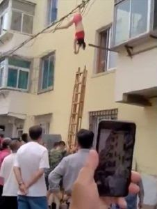 Disturbing footage has shown a woman hanging by her foot from an electricity pylon after apparently leaping from a window. According to The Sun UK the lady who is pictured wearing only her underwear is believed to have mistakenly jumped when her boyfriends wife returned home. The shocking clip is thought to have been filmed somewhere in China and shows a crowd of people watching and filming the bizarre scene.  A long ladder is shown being rested against the wall nearest the woman in a bid to…
