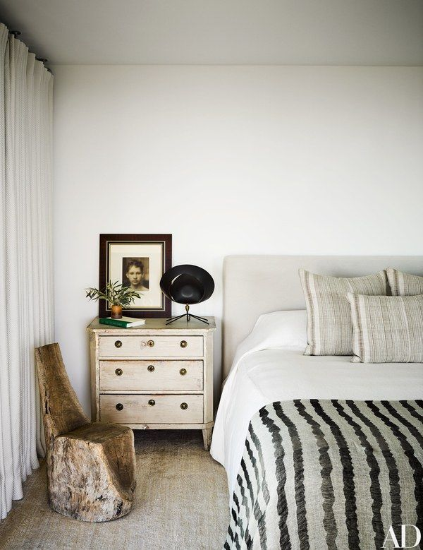 A guest bedroom is furnished with an antique wood stump chair, a Gustavian commode, and a Saturne lamp by Serge Mouille | archdigest.com