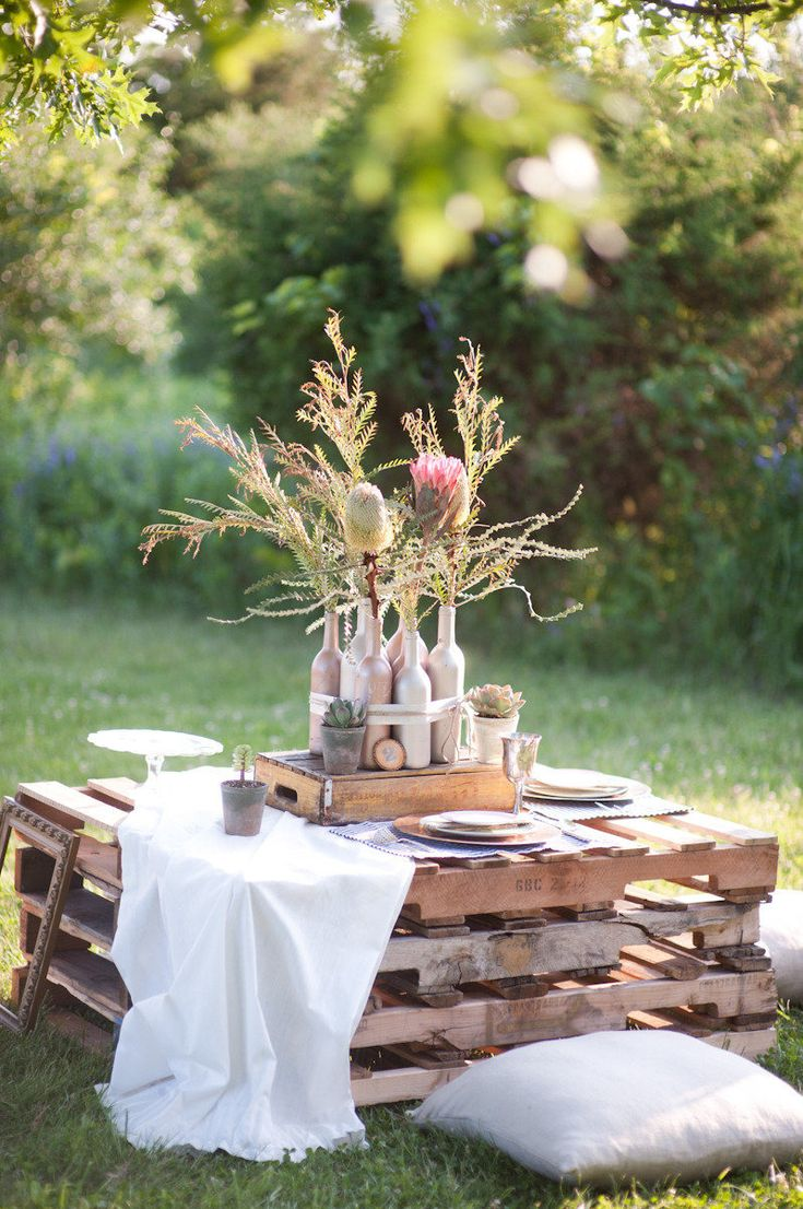 love this for cocktail tables- pallets, simple white linene, protea
