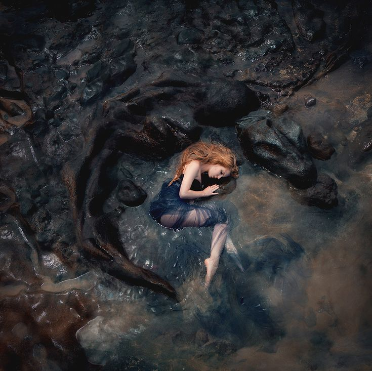 ''Peaceful and curled into the rocks....porcelian skin her clothing tattered...she shows no sign of life...the current of the ocean to strong...poor beautiful ''Red' that's what they called her...she is lost to us forever....