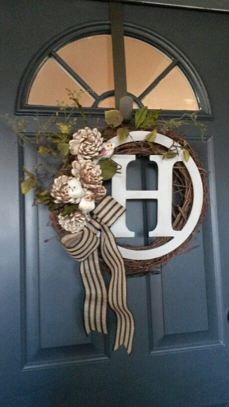 Grapevine wreath with painted initial circle, wood roses, owls and simple striped burlap bow.