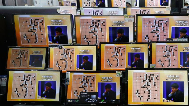 South Korean professional Go player Lee Sedol is seen on TV screens during the Google DeepMind