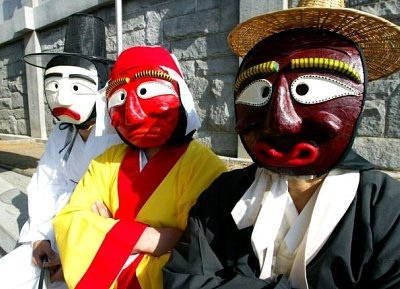 Three mask-dancers in full costume wait to perform at a Korean culture festival, wearing brightly-painted wooden masks.