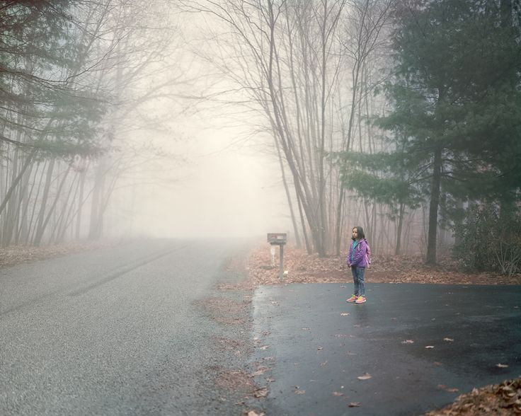 """""""The Bus Stop Between Two Worlds,"""" a photo series by Greg Miller. A photographer took pictures of children in his hometown as they waited at their bus stop.  Notice the contrast of scale between the subject and the path behind her. The distance behind her suggests that, unlike the previous subject, her house if off the beaten path."""