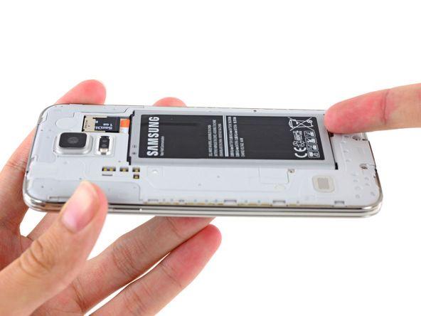 2. Trykk et plaståpningsverktøy inn i fordypningen eller bruk en negl for å løfte opp batteriet.