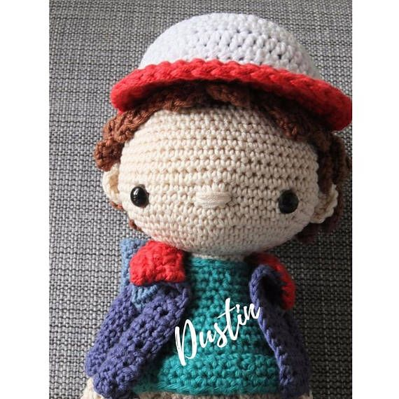 This cute little Stranger things Dustin doll is handcrafted using recycled 100% cotton yarn, stuffed with fibre fill. Dustin stands stands about 13 inches / 33 cm tall from the top of his cap to the bottom of his baseball boots. He is wearing a little removable backpack for all his