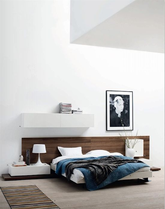 Natural wood headboard that contrasts nicely with the stark white walls and furniture. I enjoy the pop of darker teal and the charcoal throw that balance out the darker headboard and at the same time breathe some sophisticated life into the otherwise listless room.