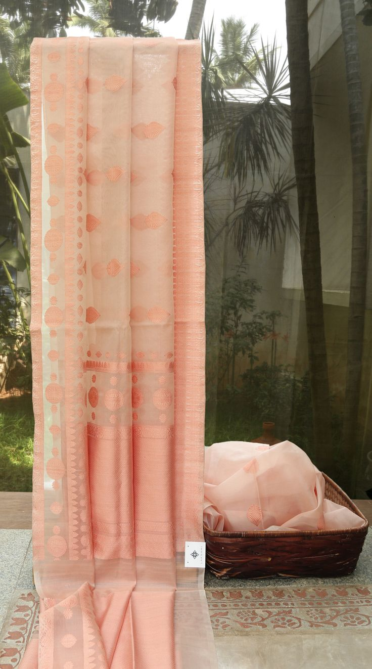 This pretty benares kora is in salmon pink with¾ bhuttas in similar toned thread work. The complementing border and pallu are also in salmon pink with beautiful texturing and finely woven bhuttas i…