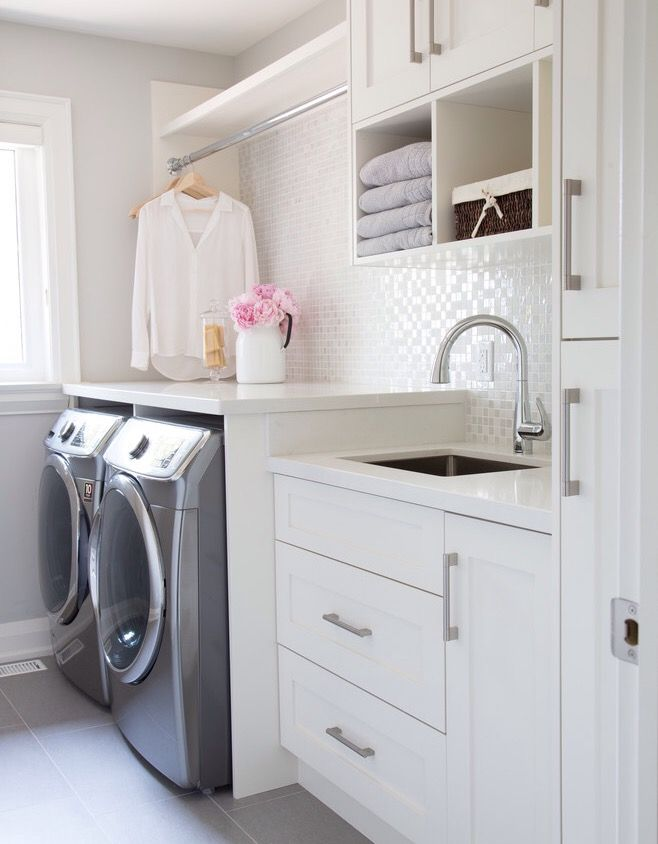 All white laundry room bliss! Love the sparkly white tile giving some glam to a utilitarian space & the must have hanging rack.