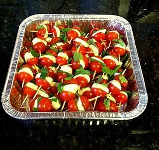 MINI CAPRESE APPETIZERS.  Sliced fresh marinated mozzarella and basil leaves on a toothpick between split cherry tomatoes, drizzled with balsamic vinegar.