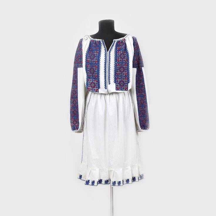 Romanian blouse from Muscel   Cămaşă femeiască cu poale, de Muscel. Piesa este o interpretare modernă de vestimentaţie feminină - rochie, obţinută prin transferul broderiei tradiţionale de la o ie de Muscel. Au fost păstrate croiul şi decorul tradiţionale ale cămăşii, cu mânecile amplu brodate (altiţă şi trei râuri) strânse pe manşetă, piepţii şi spatele.  Ultimul pătrar al sec. XX, Câmpulung Muscel