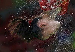 Fan Yilin of China as chalk flies from the uneven bars.
