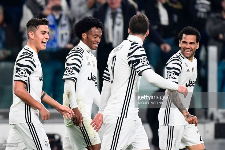 Juventus' forward from Argentina Paulo Dybala (L) celebrates with teammates Juventus' forward from Colombia Juan Cuadrado (2ndL), Juventus' forward from Argentina Gonzalo Higuain and Juventus Defender from Brazil Dani Alves (R) after scoring a penalty during the UEFA Champions League football match Juventus vs FC Porto on March 14, 2017 at the Juventus stadium in Turin. /