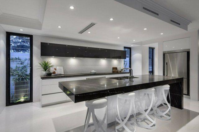 une cuisine blanche avec des armoires noires et un comptoir en marbre noir