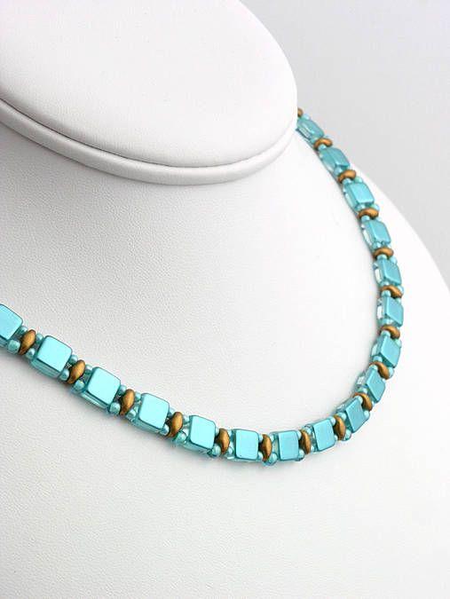Náhrdelník šitý zo zlatých voskovaných matných korálok a tyrkysových štvorčekov. Zapínanie z bižutérneho kovu...