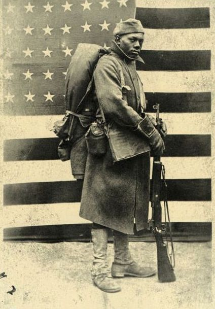 WORLD WAR I: African American infantryman posing in front of the American flag.  fighting for the country that still segregated him from whites!??