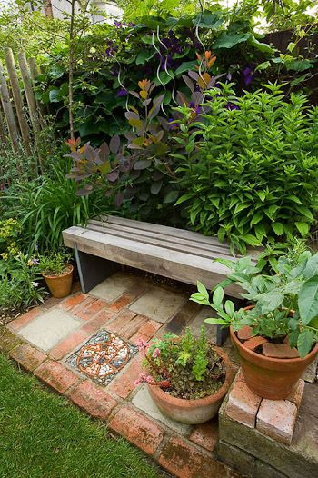 Restful garden spot | Garden Bench with its own patchwork mini patio floor, set amongst lush green shrubbery| n.b. - Place in front of photinia grouping in BACKYARD
